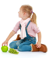 Little girl sitting on the floor and holding a hand an apple.