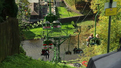 Cable way over river, people tourists ascending descending cabin