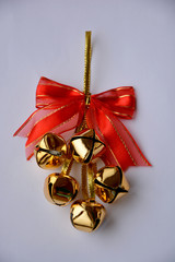 Golden jingle bells with red bow, isolated on white background