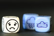 concept of sad autumn weather - emoticon and weather dice on bla