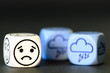 concept of sad storm weather - emoticon and weather dice on blac