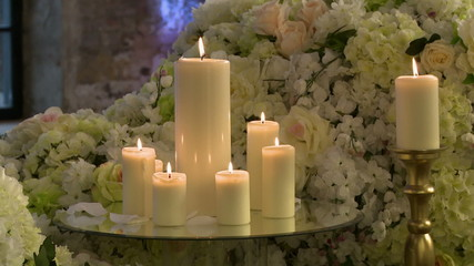 Lighted candles on backdrop of floral composition
