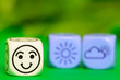 concept of good  summer weather - emoticon and weather dice on g