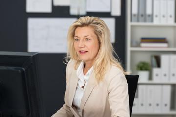 geschäftsfrau im büro schaut auf ihren computer