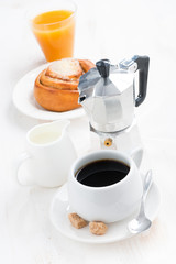 breakfast with coffee, sweet bun, cream and orange juice