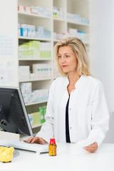 apothekerin schaut nach medikament im computer