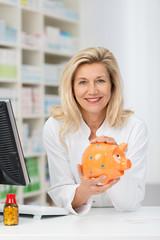 lächelnde apothekerin hält sparschwein in händen