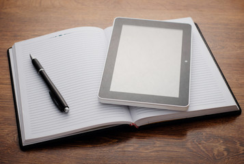 Tablet Device on Open Notebook at Wooden Table