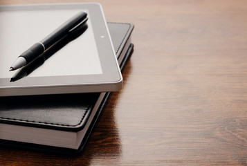 Tablet Device on Notebook at Wooden Table