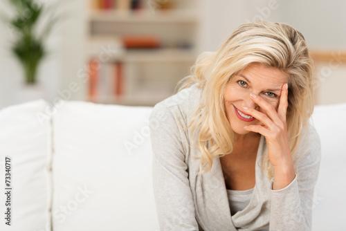 Leinwanddruck Bild moderne ältere frau stützt lächelnd den kopf auf