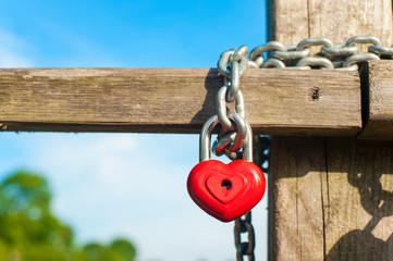 Love heart shape lock with chain on wooden bridge.