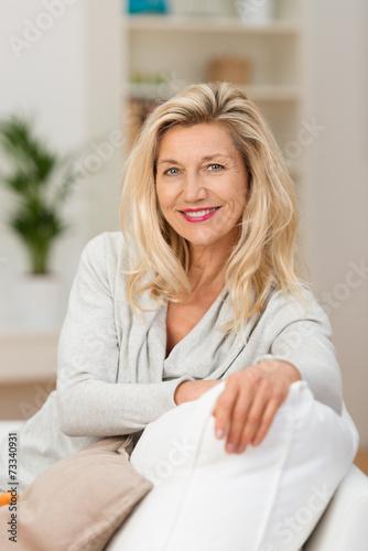 Leinwanddruck Bild schöne frau sitzt entspannt auf dem sofa