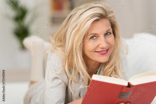 Leinwanddruck Bild entspannte frau liest ein buch auf dem sofa