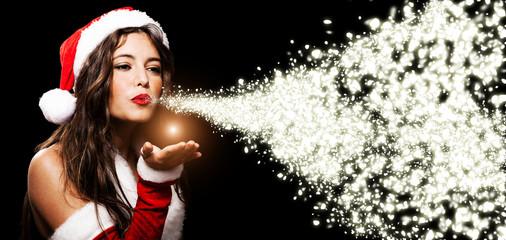 Christmas girl blowing shining snow flakes
