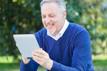 Smiling man using his tablet
