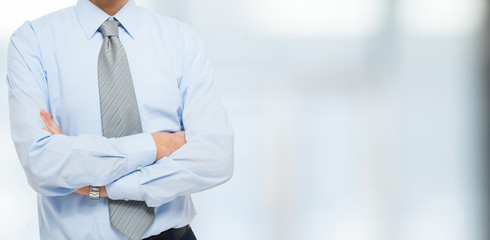 Businessman with folded arms, large copyspace