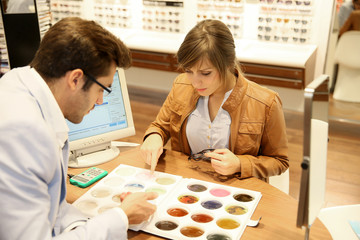 Woman with optician choosing spectacle lenses colour