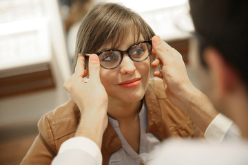 Young woman with optician in optical shop trying eyeglasses