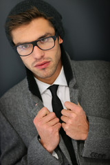 Model with eyeglasses and winter coat on black background
