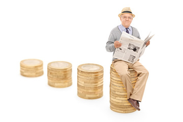 Senior reading the news seated on a pile of coins