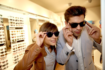 Trendy couple in optical shop choosing sunglasses