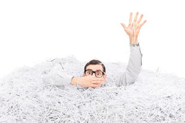 Man drowning in a pile of shredded paper