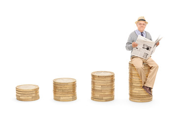 Pensioner reading the news on a pile of coins