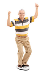 Joyful senior standing on a weight scale
