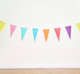 Birthday decoration flags on a plain white wall