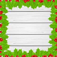 Christmas frame of holly berries on wooden background