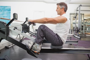 Fit man working out on rowing machine