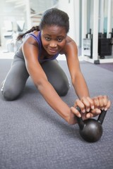 Fit woman working out with kettlebell