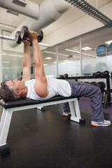 Fit man lifting dumbbell lying on the bench