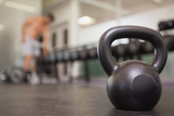 Focus on large black kettlebell in weights room