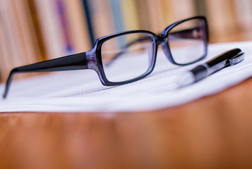 Eyeglasses and Pen on Top of White Paper