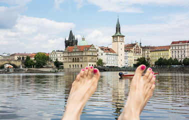 Female legs with painted nails and cityscape of Prague with Vlta