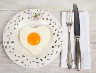 Herzförmiges Spiegelei auf weißen Teller