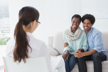 Reconciled couple smiling at their therapist