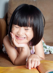 Asian little girl happy to reading  book