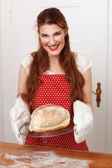 Junge Frau hält warmes Brot