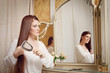 canvas print picture - Junge Frau bürstet sich die Haare vor Spiegel