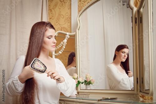 canvas print picture Junge Frau bürstet sich die Haare vor Spiegel
