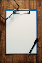 Eye-glasses and a black pen on an empty white page