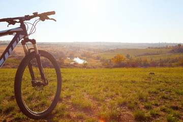 Mountain bicycle stands on the off-roads on  the river backgroun