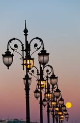 Big moon against decorative streetlights
