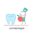 stomatologist    with apple standing near a large tooth