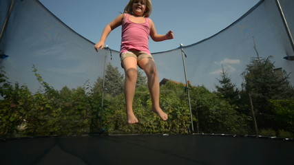 Happy girl jumping in the trampoline