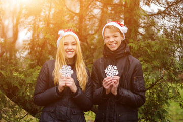 Happy young couple in love wearing Santa hats and holding big