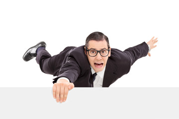 Businessman hanging on the edge of a white panel