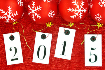 New year 2015 on tags and Christmas balls on red background